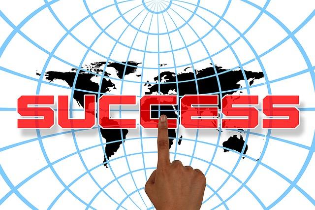 """prst ukazující na nápis """"úspěch"""" na pozadí světové sítě"""
